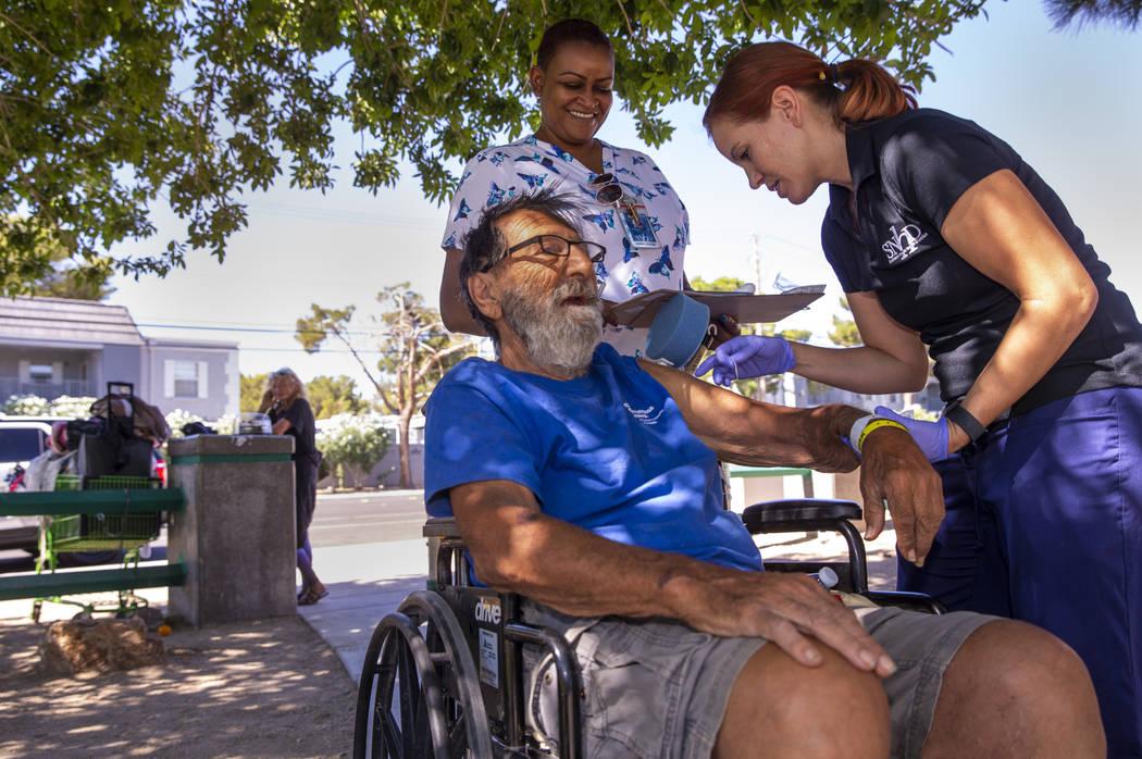 Homeless man Elias Sayegh, left, receives a Hepatitis A shot from Sarah Lugo, Southern Nevada H ...