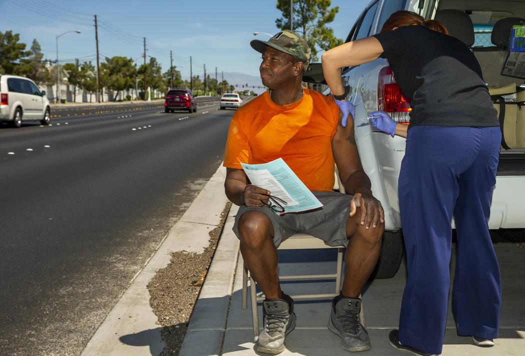 Sarah Lugo, Southern Nevada Health District senior community health nurse, administers a shot t ...