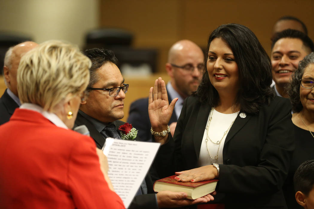 New Councilwoman Olivia Diaz, right, with her husband Frank, center, is sworn into office by Ma ...