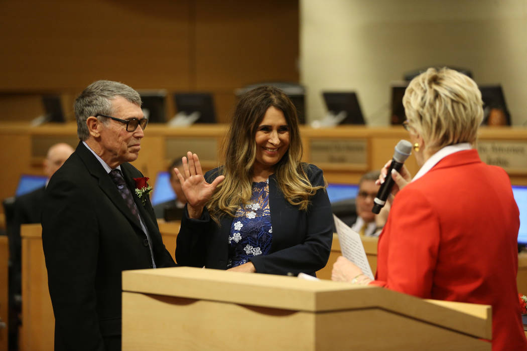 New Councilwoman Victoria Seaman, center, with her husband John Seaman, left, is sworn into off ...