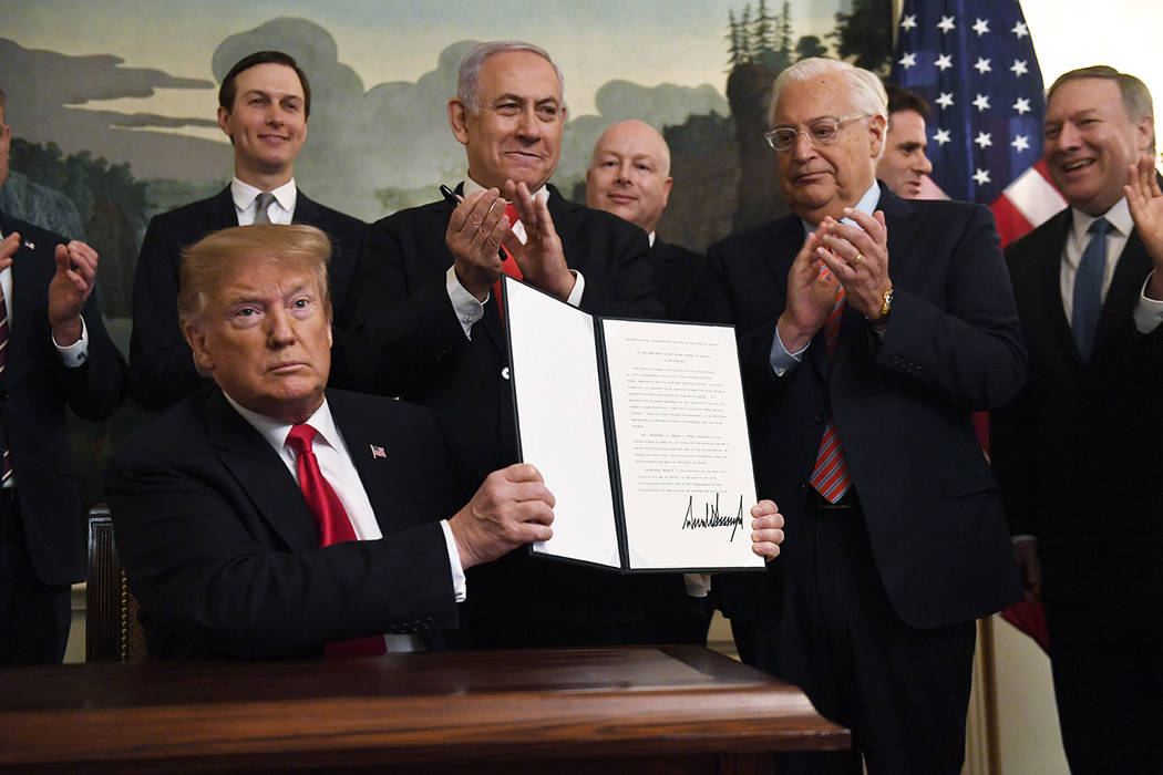 President Donald Trump holds up a signed proclamation recognizing Israel's sovereignty over the ...