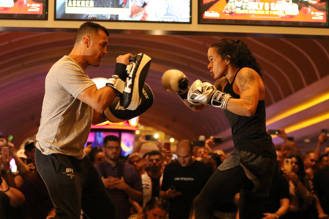 UFC women's bantamweight and featherweight champion Amanda Nunes, right, hits mitts with her co ...
