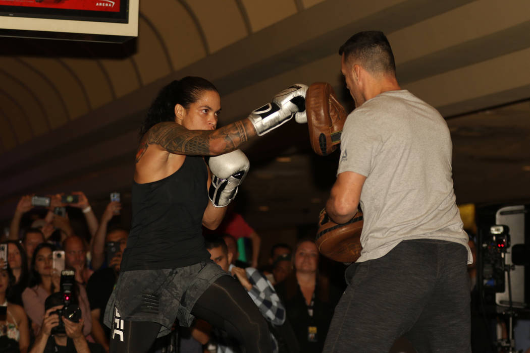 UFC women's bantamweight and featherweight champion Amanda Nunes, left, hits mitts with her coa ...