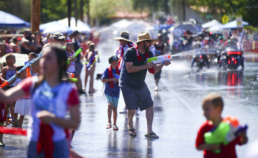 Spectators partake in water fights during the parade at the annual Damboree Celebration in Boul ...