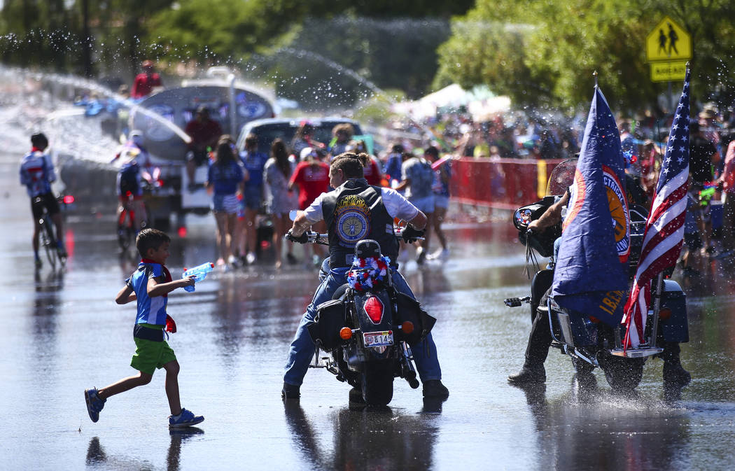 A child runs past a pair of parade participants on motorcycles, representing the International ...