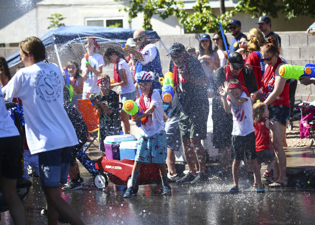 Parade spectators partake in water fights during the parade at the annual Damboree Celebration ...