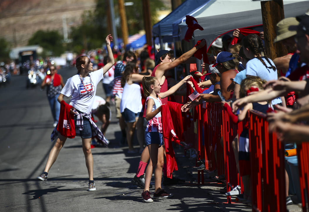 Wet towels are passed out by supports of Boulder Dam Credit Union during the parade at the annu ...