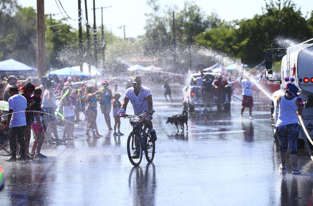 A man rides a bicycle as spectators and parade participants spray water during the parade at th ...