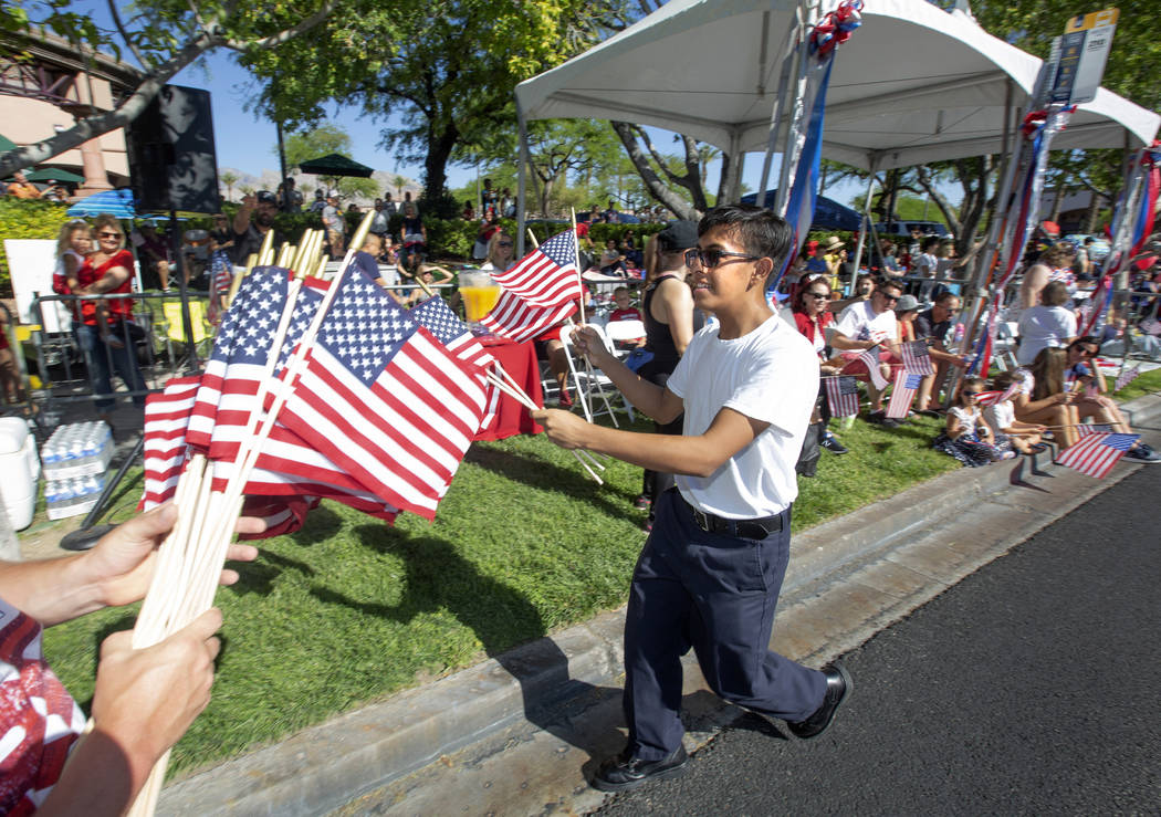 Angel Lemurs, 16, hands out American flags during the 25th annual Summerlin Council Patriotic P ...