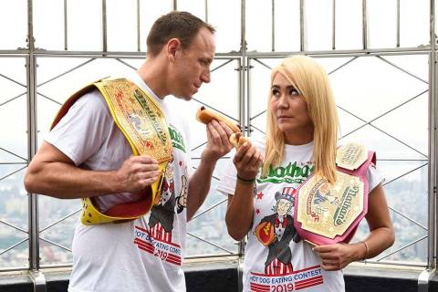 Eleven-time and defending men's champion Joey Chestnut, left, and defending women's champion Mi ...