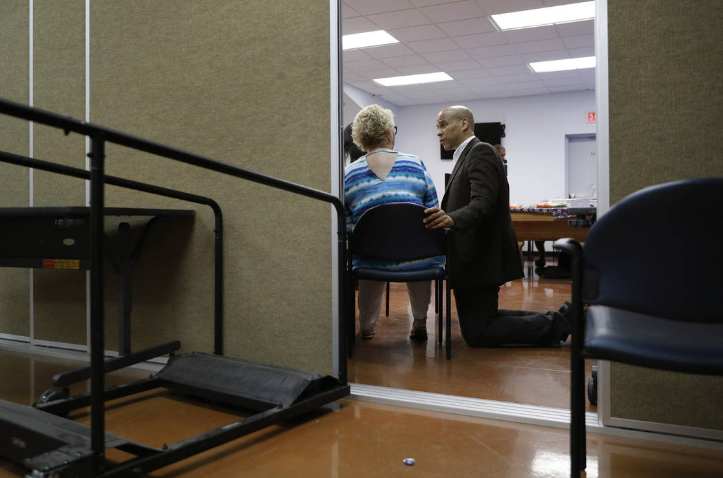 Democratic presidential candidate Sen. Cory Booker, right, speaks with Liz Geffon at a Veterans ...