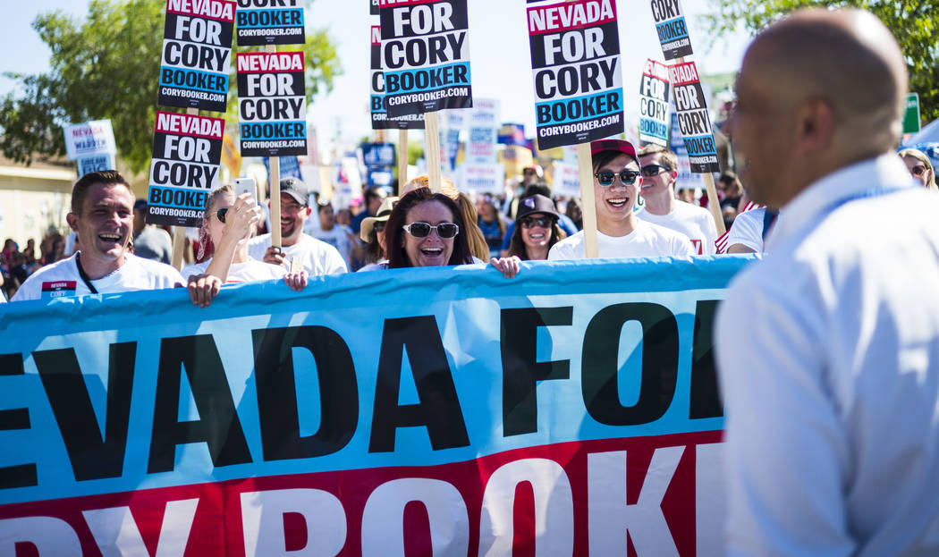 Supporters march in a parade with Democratic presidential candidate Sen. Cory Booker, D-N.J., d ...