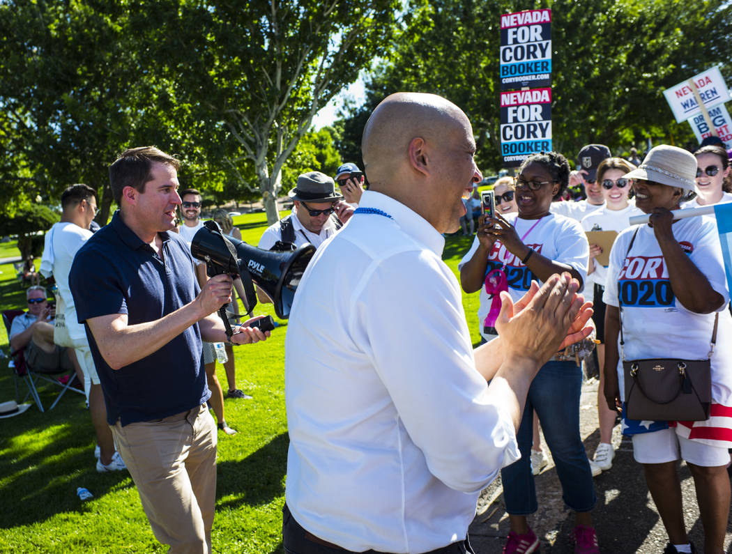 Rep. Seth Moulton, D-Mass., left, talks as Democratic presidential candidate Sen. Cory Booker, ...