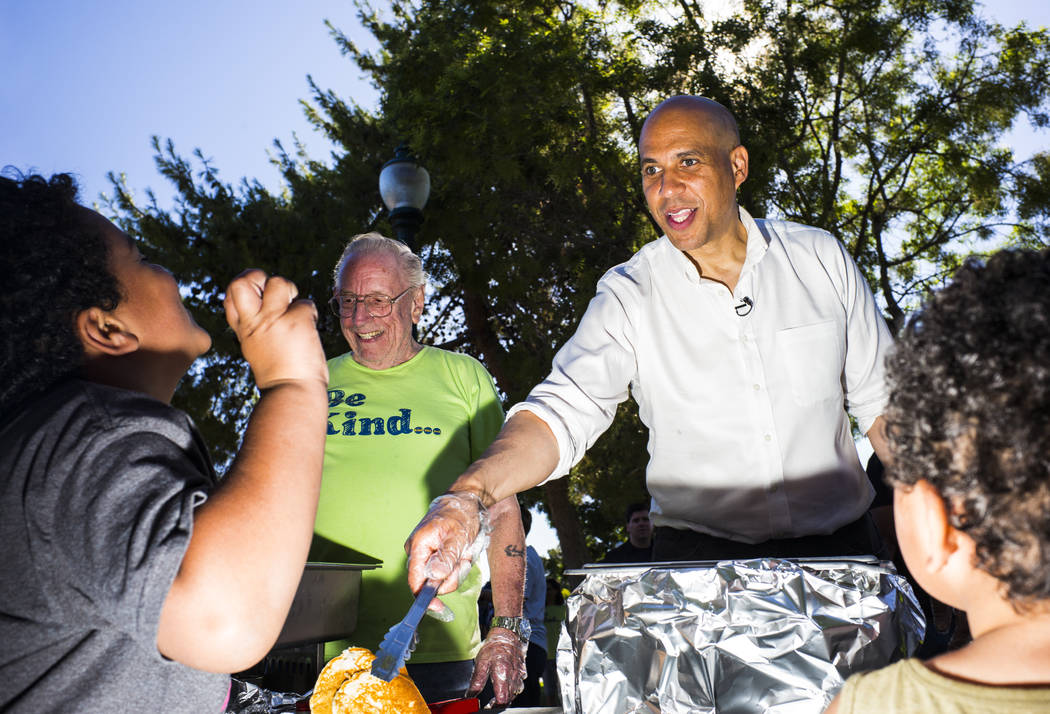 Democratic presidential candidate Sen. Cory Booker, D-N.J., serves pancakes while attending a b ...