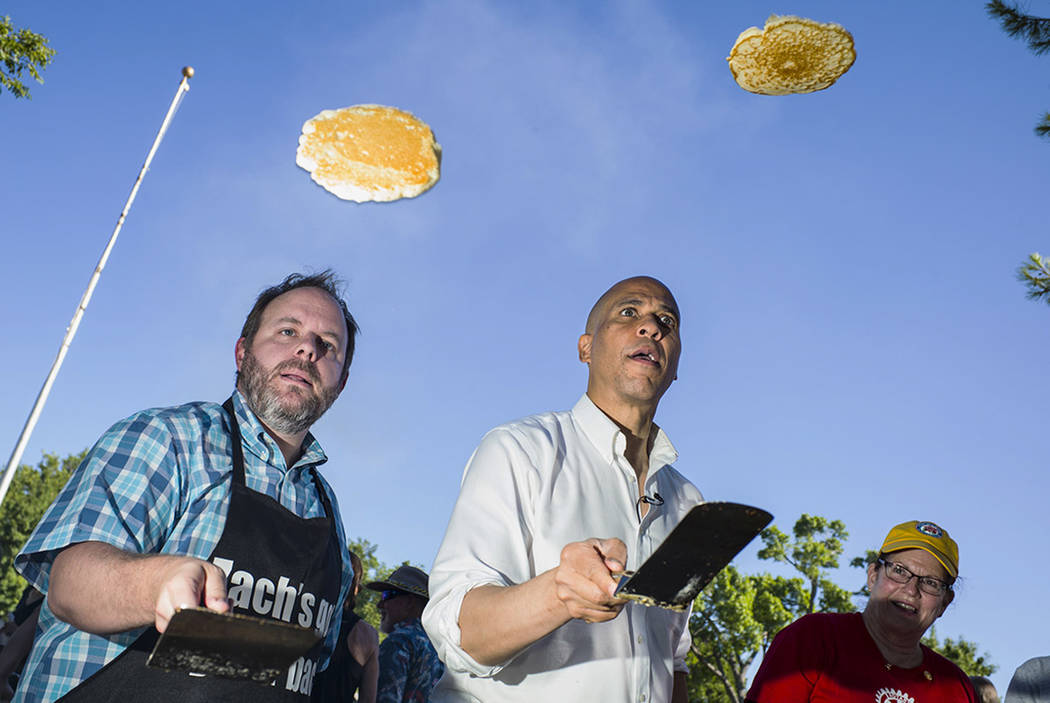 Nevada Treasurer Zach Conine, left, flips pancakes with Democratic presidential candidate Sen. ...