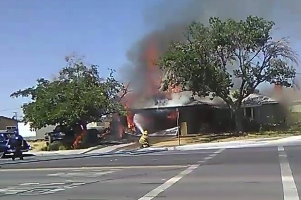 In this image taken from video provided by Ben Hood, a firefighter works to extinguish a fire, ...