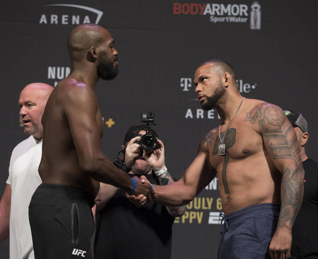 UFC light heavyweights Thiago Santos, right, shakes hands with Jon Jones during weigh ins for U ...