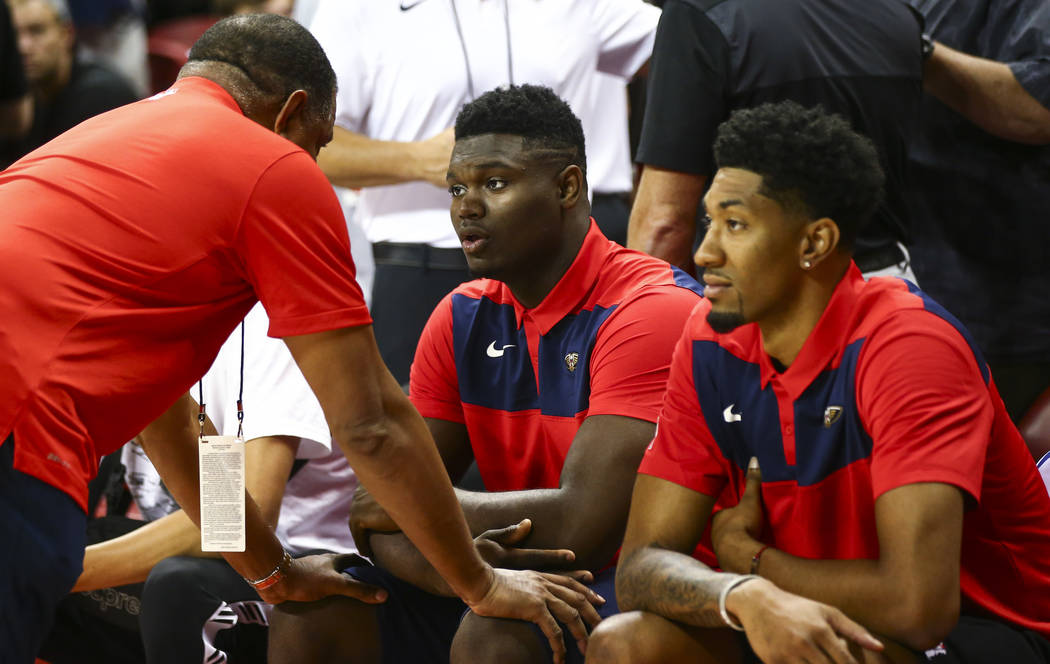 New Orleans Pelicans' Zion Williamson, center, talks with a member of staff on his team before ...