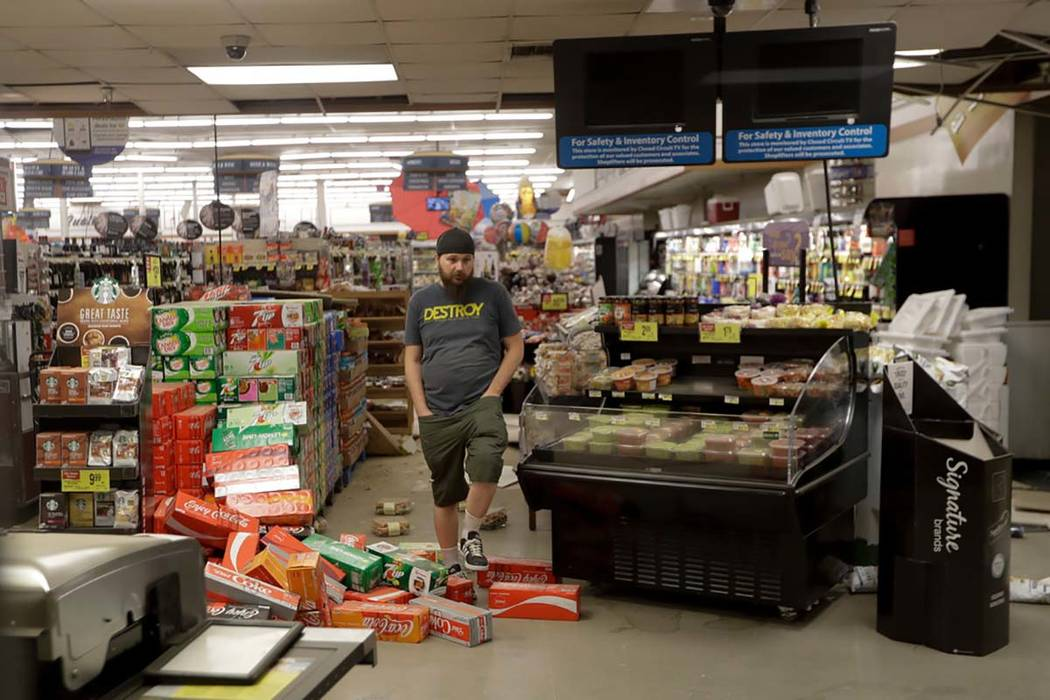 A worker steps over merchandise that is scattered on the floor of a Albertson's grocery store S ...