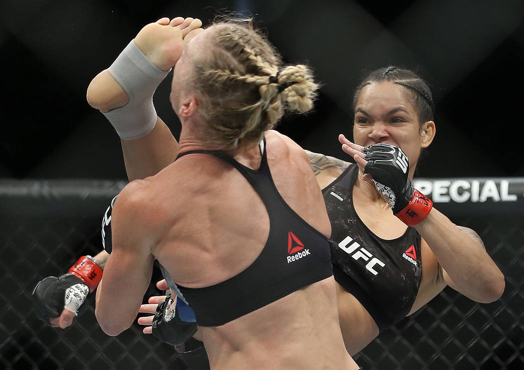 Amanda Nunes, right, connects with a high kick against Holly Holm in the first round during the ...