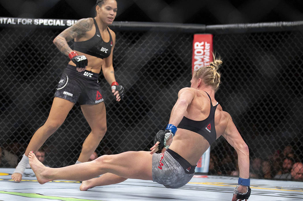 Amanda Nunes, left, knocks out Holly Holm with a kick during the first round of their women's b ...