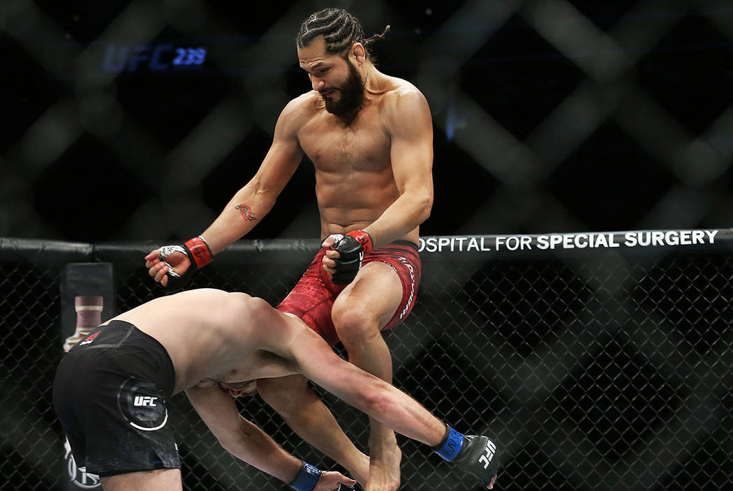 Jorge Masvidal, right, connects with a flying knee against Ben Askre in the first round during ...