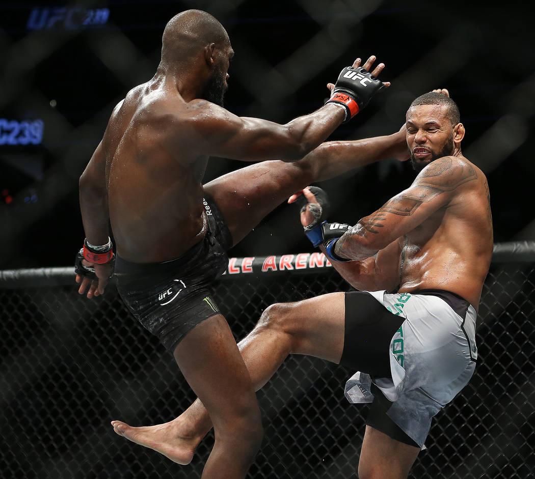 Jon Jones, left, lands a high kick against Thiago Santos in the first round during their light ...