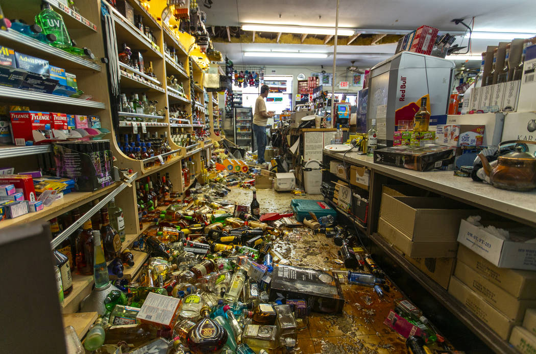 Employees continue to sell gas and food items as wine bottles and other merchandise are scatter ...