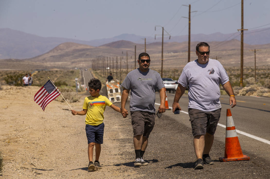 (From left) Aiden Dadebhoy, 8, and his father Zeshan walk with Tom Velez as they look to view t ...