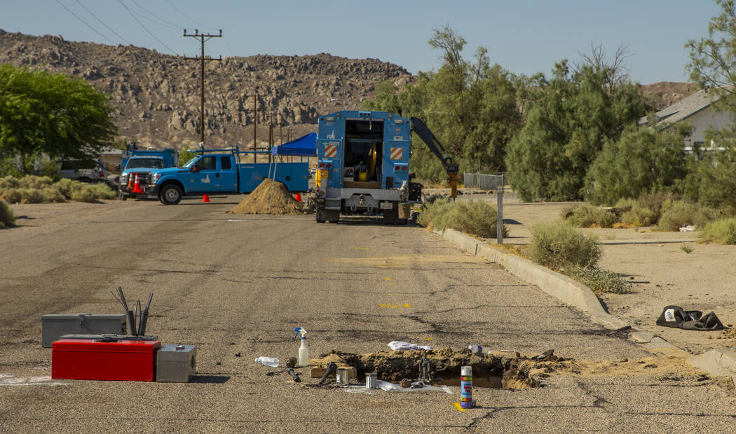 An open hole revealing a broken gas line is repaired by a PG&E crew in Trona, CA., due to t ...