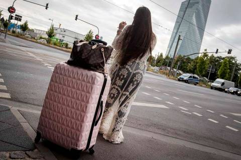 A woman stands with her suitcase near the European Central Bank as 16 000 people are evacuated ...