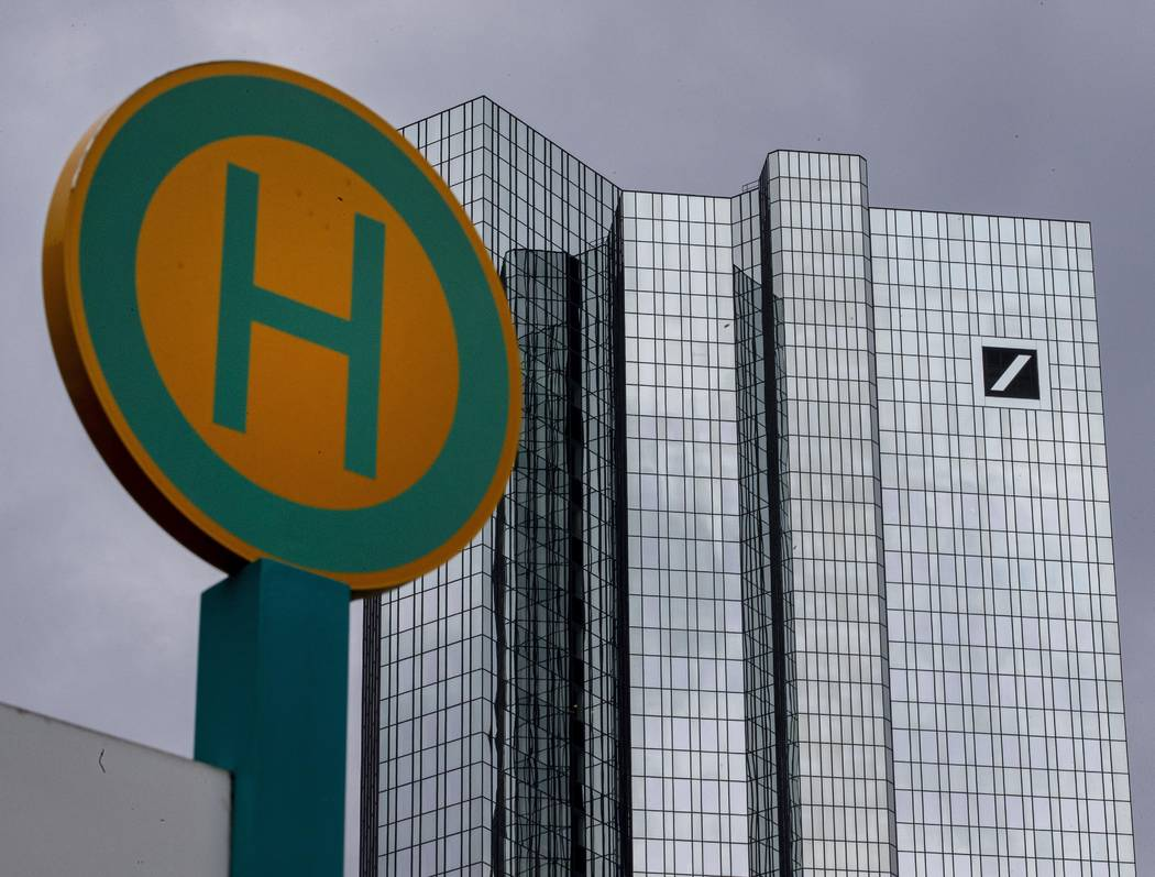 The headquarter of Deutsche Bank is seen next to a bus stop sign in Frankfurt, Germany, Sunday, ...