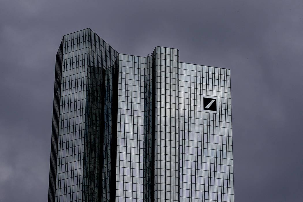 Dark clouds cover the sky over the headquarter of Deutsche Bank in Frankfurt, Germany, Sunday, ...