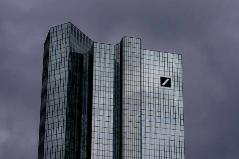 Dark clouds cover the sky over the headquarter of Deutsche Bank in Frankfurt, Germany, Sunday, ...