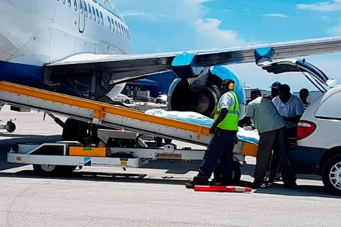 In this handout photo released by the Bahamas ZNS Network, employees oversee the arrival of the ...