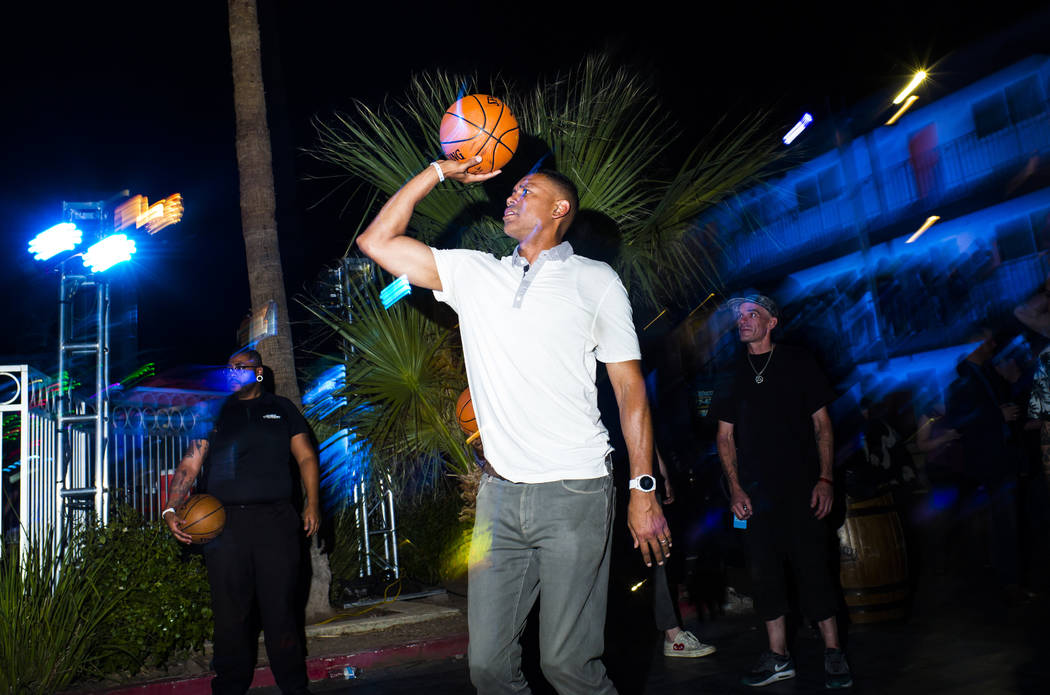 Former NBA player Allan Houston, center, shoots a basket during the Jack Daniel's House No. 7, ...