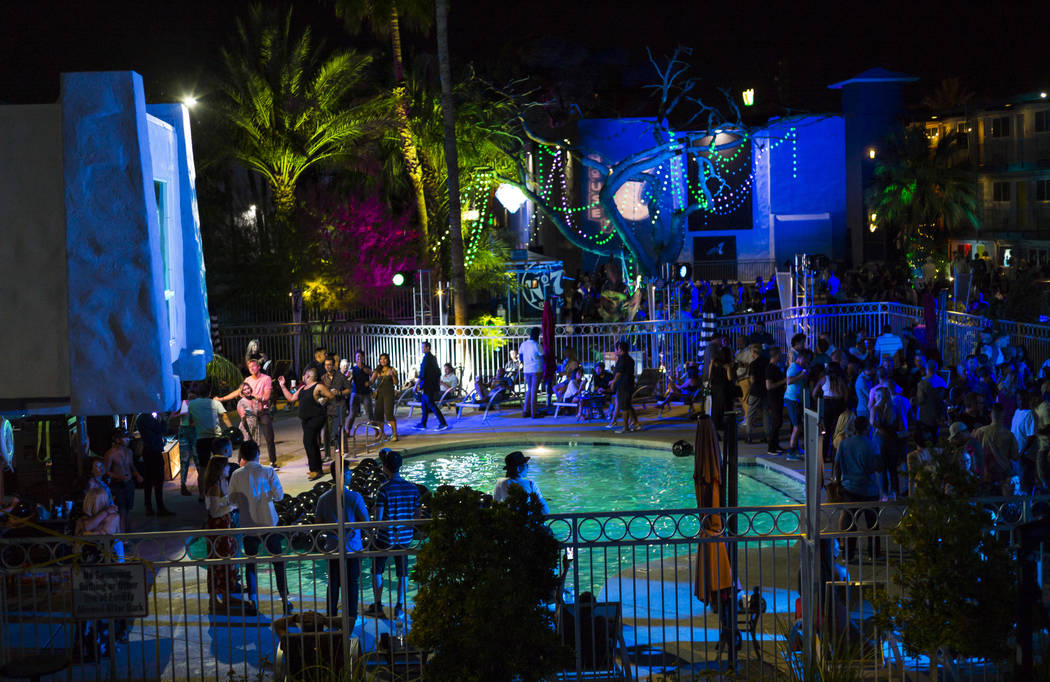 Attendees gather around the pool area for a drag show performance during the Jack Daniel's Hous ...