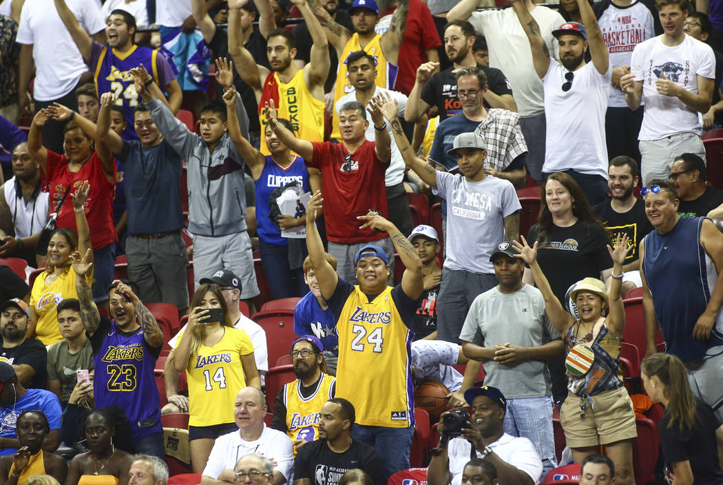 Basketball fans cheer for free items during a game between the Los Angeles Lakers and the Los A ...