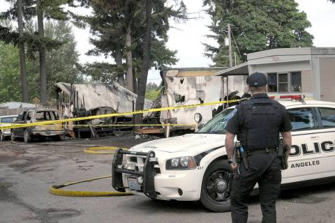 Port Angeles police Officer T.J. Mueller looks over the scene of a fire that destroyed two mobi ...