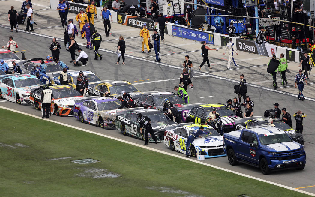 Pit crews begin to cover their cars on pit road as inclement weather moves in causing a delay i ...