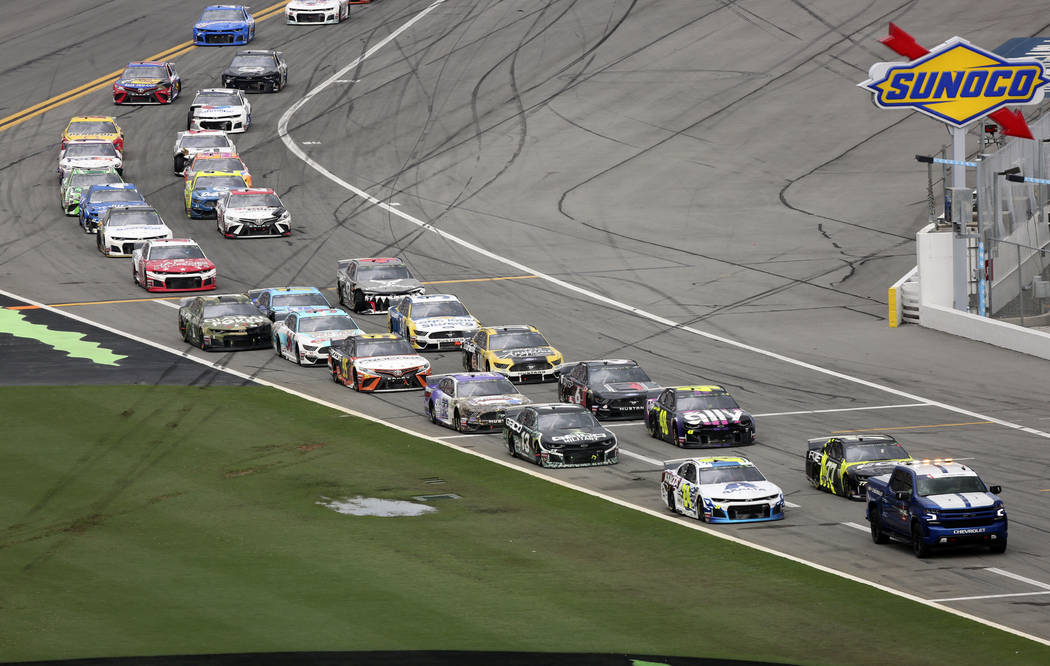 Cars file in behind the pace truck on pit road after the NASCAR Cup Series auto race was delaye ...
