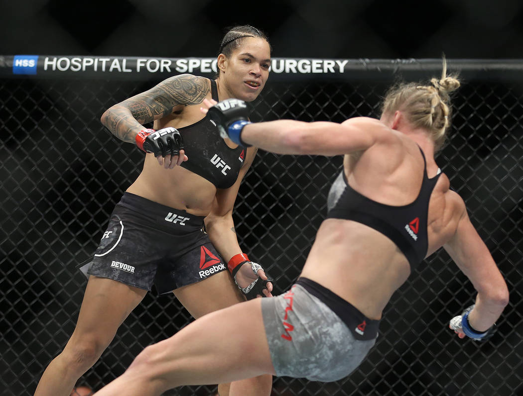 Amanda Nunes, left, watches Holly Holm fall after connecting with a high kick in the first roun ...