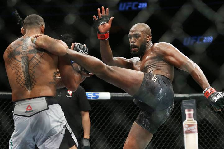 Jon Jones, right, lands a high kick against Thiago Santos in the first round during their light ...