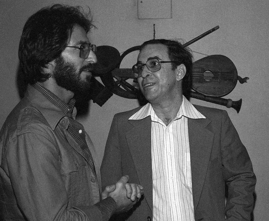 FILE - In this July 1978 file photo, Brazilian Joao Gilberto, right, chats backstage with a fan ...