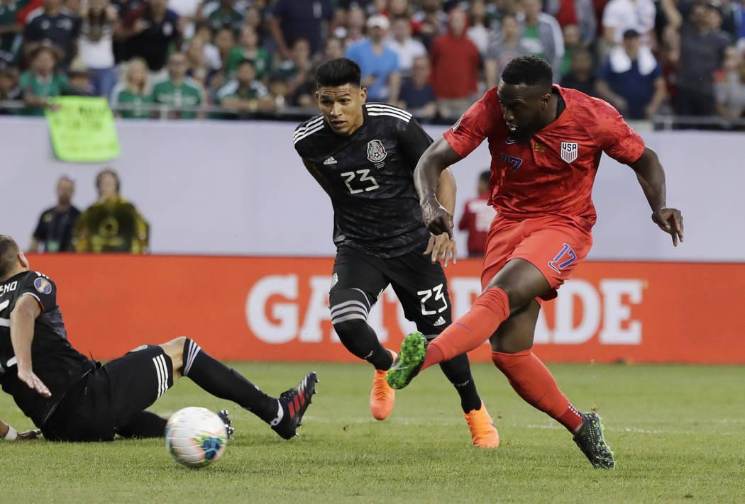 United States forward Jozy Altidore, right, shoots against Mexico midfielder Jesus Gallardo dur ...