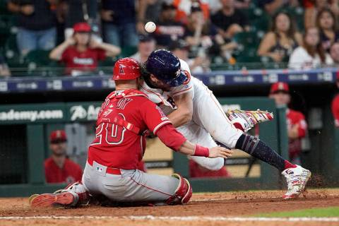 Houston Astros' Jake Marisnick, right, collides Los Angeles Angels catcher Jonathan Lucroy (20) ...