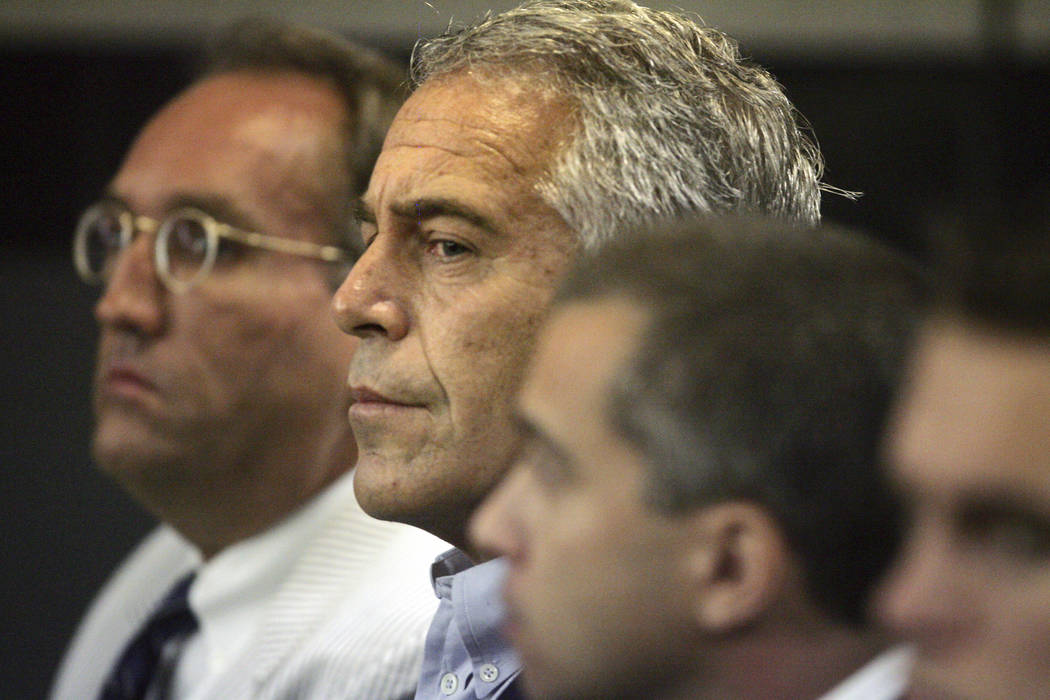 In a July 30, 2008, file photo, Jeffrey Epstein, center, is shown in custody in West Palm Beach ...