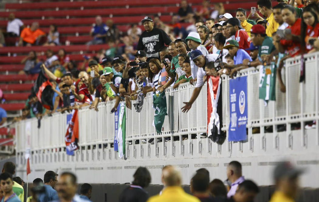 Soccer fans cheer as plays from Leon and Tijuana enter the field for an exhibition soccer match ...