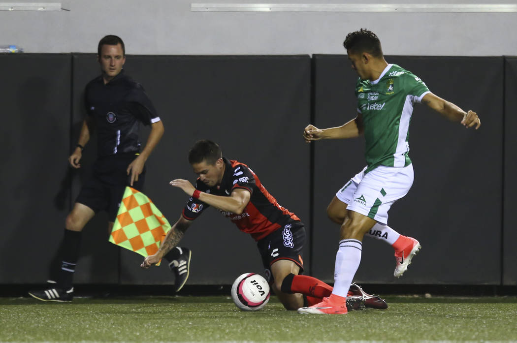 Tijuana's Damian Perez, left, is tripped up by Leon's Andres Andrade during an exhibition socc ...