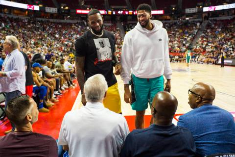 Los Angeles Lakers' LeBron James and Anthony Davis talk with Jerry West, of the Clippers, seate ...